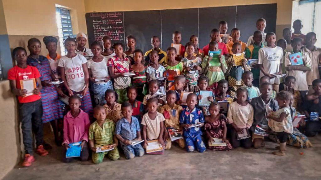 Photo de groupe des enfants devant le tableau noir de l'école